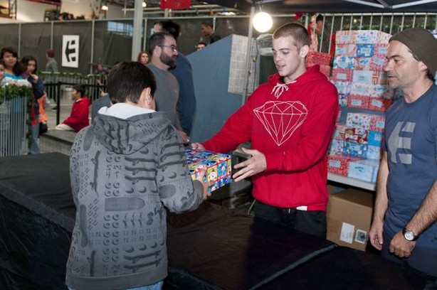 Ryan Sheckler hands out shoes to kids.