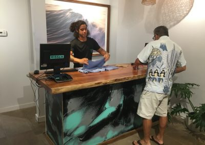 Store manager Moises Nava helping a customer. The POS counter is made from Koa log from the Big Island.
